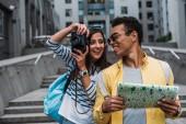 Žena fotografuje na digitálním fotoaparátu a dívá se na dvourasový přítel držící mapu