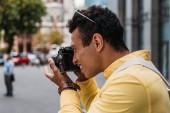 Multiracial Mann, der Foto auf Digitalkamera in der Stadt