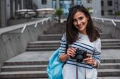 Žena v neformálním batohu s digitálním fotoaparátem a s úsměvem