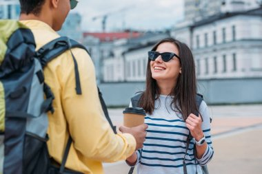 Smiling woman with sunglasses looking at bi-racial friend with coffee paper cup and backpack