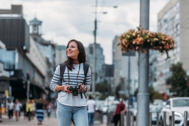 Smiling woman with digital camera looking away with backpack