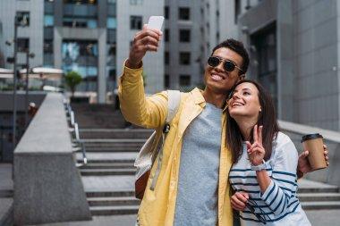 Bi-racial man in sunglasses with woman taking selfie on smartphone stock vector