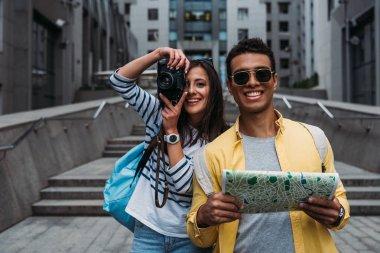 Woman taking photo on digital camera near bi-racial friend holding map stock vector