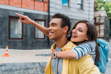 happy girl hugging cheerful mixed race man and pointing with finger near building