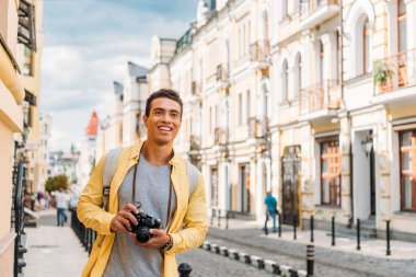 Cheerful mixed race man smiling while holding digital camera near buildings stock vector
