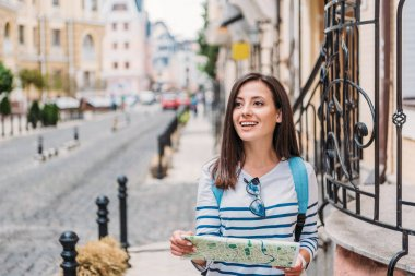 happy young woman holding map and smiling on street