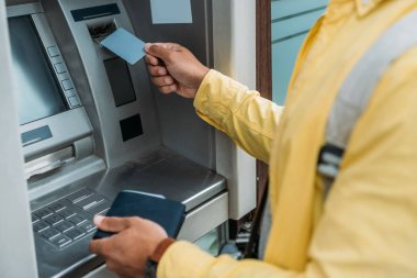 cropped view of mixed race man putting credit card in atm machine while holding wallet