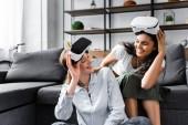 multikulturelle Freunde mit Virtual-Reality-Headsets, die einander anlächeln und anschauen