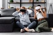 Multikulti-Freunde mit Virtual-Reality-Headsets sitzen in Wohnung auf dem Boden