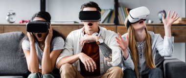 panoramic shot of multicultural friends with virtual reality headsets