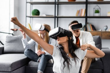 Selective focus of multicultural friends with virtual reality headsets sitting on sofa stock vector