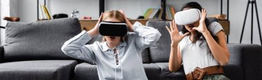 panoramic shot of multicultural friends with virtual reality headsets in apartment