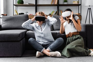 multicultural friends with virtual reality headsets sitting on floor in apartment
