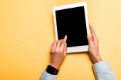 Ausgeschnittene Ansicht eines Mädchens, das mit dem Finger auf ein digitales Tablet mit leerem Bildschirm auf orange zeigt