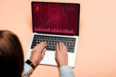 cropped view of woman typing on laptop with trading charts and graphs on pink