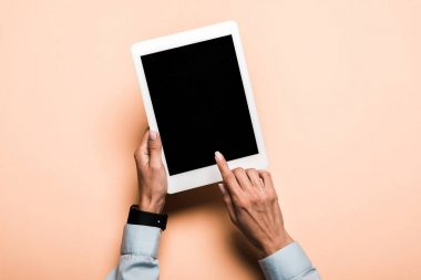 cropped view of woman pointing with finger at digital tablet with blank screen on pink