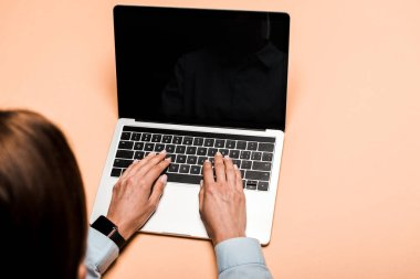 cropped view of woman typing on laptop with blank screen on pink