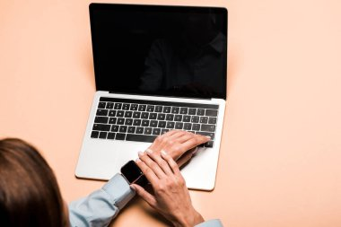 cropped view of woman touching smart watch near laptop with blank screen on pink