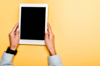 cropped view of girl holding digital tablet with blank screen on orange