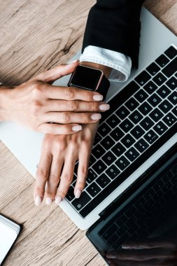 top view of woman touching smart watch near laptop
