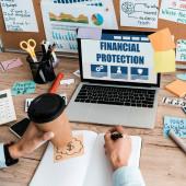 oříznutý pohled na ženu s perem a papírovým šálkem blízko notebooku s finanční ochranou na obrazovce