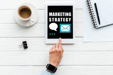 """Картина, постер, плакат, фотообои """"верхний вид женщины, указывающей пальцем на цифровой планшет с маркетинговой стратегией надписи на экране возле чашки кофе и скрепки """", артикул 298083330"""
