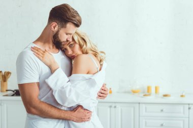 beautiful young woman looking at camera while embracing with boyfriend in kitchen