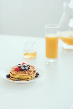 selective focus of plate with tasty pancakes and berries near glass and jug of orange juice and jar with honey on white table