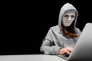anonymous internet troll in mask typing on laptop keyboard isolated on black