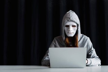 anonymous internet troll in mask typing on laptop keyboard on black
