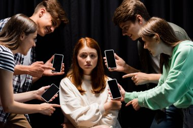 smiling teenagers pointing with fingers at girl during bullying and holding smartphones with blank screen on black