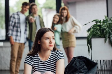 selective focus of group of teenagers bullying sad girl in school