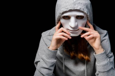 anonymous girl in grey hoodie and mask isolated on black