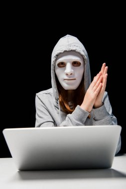 front view of anonymous girl in mask and hoodie sitting near laptop and rubbing hands during cyberbullying isolated on black