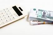 moderní kalkulačka s tlačítky v blízkosti ruských peněz na bílém