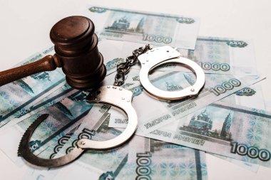 wooden gavel near handcuffs on russian money