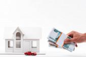 oříznutý pohled člověka držímající ruské peníze v blízkosti hračkářského vozu a cartonova domu na bílém