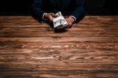 režijní pohled na člověka držící ruské peníze blízko stolu