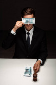 Richter bedeckt Augen mit Bestechungsgeld, während halten gavel auf schwarz