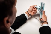 selective focus of businessman in handcuffs holding bribe on white