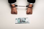 top view of businessman in handcuffs near russian money on white