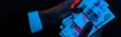 Fényképek panoráma lövés férfi gazdaság orosz pénz mellett kék UV fény izolált fekete