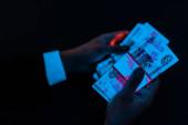 Fényképek vágott kilátás az ember, aki az orosz pénzt a kék UV fény izolált fekete