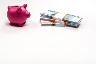 Pink piggy bank near stacks of russian money on white stock vector