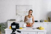 Fotografie selektivní zaměření šťastné dívky nalévání lichotníku ve skle blízko digitálního fotoaparátu