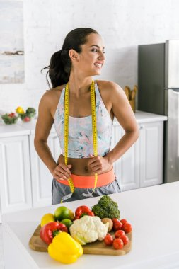 cheerful woman holding measuring tape near fruits