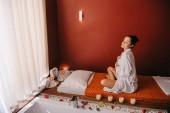 atraktivní žena se zavřenýma očima v županu a sedí na masážní rohoži