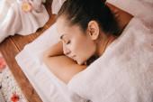 přitažlivá žena s zavřenýma očima položených na masážní rohoži