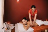 asijský masér vrací masáž ženě na masážní rohoži