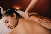 Fotografie abgeschnittene Ansicht von Masseur tun Rückenmassage zu Frau auf Massagematte
